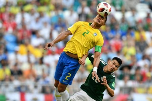 Leading from the back: captain Thiago Silva wins a high ball against Hirving Lozano in Brazil's win over Mexico
