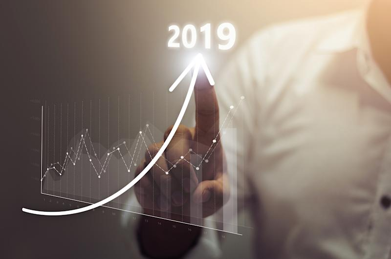 A businessman's finger tracing an upward arrow labeled 2019, with a graph showing uneven but significant growth.