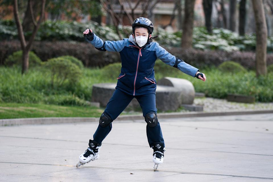 "SHANGHAI, CHINA - MARCH 05: A young boy wearing a protective mask rides roller-skates in Xujiahui Park on March 05, 2020 in Shanghai, China. Twenty-one of mainland China's 31 regions have lowered emergency response levels on the flu-like epidemic by March 1, allowing greater movement of people and goods and a recovery in business activity. Since the outbreak began in December last year, more than 80,000 cases have been confirmed in China, with the death toll rising to more than 3,000. As of today, the number of cases of new coronavirus COVID-19 being treated in China dropped to approximately 25,400 in China, in what the World Health Organization (WHO) declared to raises coronavirus threat assessment to ""very high"" across the world by the end of February. (Photo by Yifan Ding/Getty Images)"