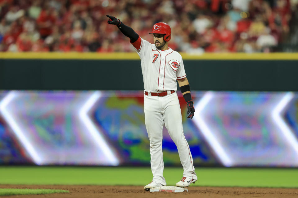 Cincinnati Reds' Eugenio Suarez points to teammates after hitting an RBI-double during the seventh inning of a baseball game against the St. Louis Cardinals in Cincinnati, Friday, July 23, 2021. (AP Photo/Aaron Doster)