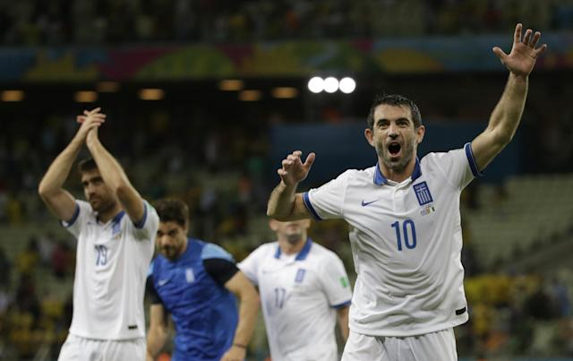 Greece's Giorgos Karagounis, right, waves to supporters as he celebrates his side's 2-1 win after the group C World Cup soccer match between Greece and Ivory Coast at the Arena Castelao in Fortaleza, Brazil, Tuesday, June 24, 2014. (AP Photo/Fernando Llano)