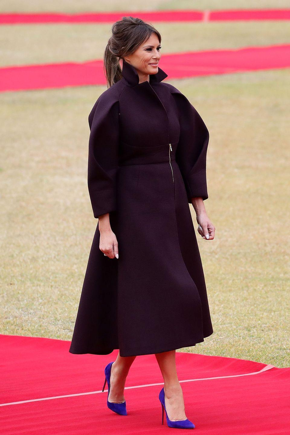 """<p>Arriving in South Korea, FLOTUS wore a deep burgundy Delpozo coat dress paired with blue-violet stiletto pumps. Look familiar? She wore a bright fuchsia dress from the brand in a similar silhouette for her <a href=""""https://www.townandcountrymag.com/society/politics/a12444274/melania-trump-united-nations-speech/"""" rel=""""nofollow noopener"""" target=""""_blank"""" data-ylk=""""slk:United Nations speech"""" class=""""link rapid-noclick-resp"""">United Nations speech</a> back in September.</p>"""