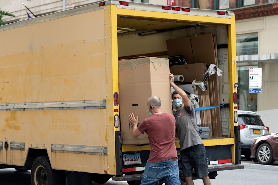 People wearing masks load a box into a moving truck as the city continues Phase 4 of re-opening following restrictions imposed to slow the spread of coronavirus on August 31, 2020, in New York City. (Photo by Alexi Rosenfeld/Getty Images)