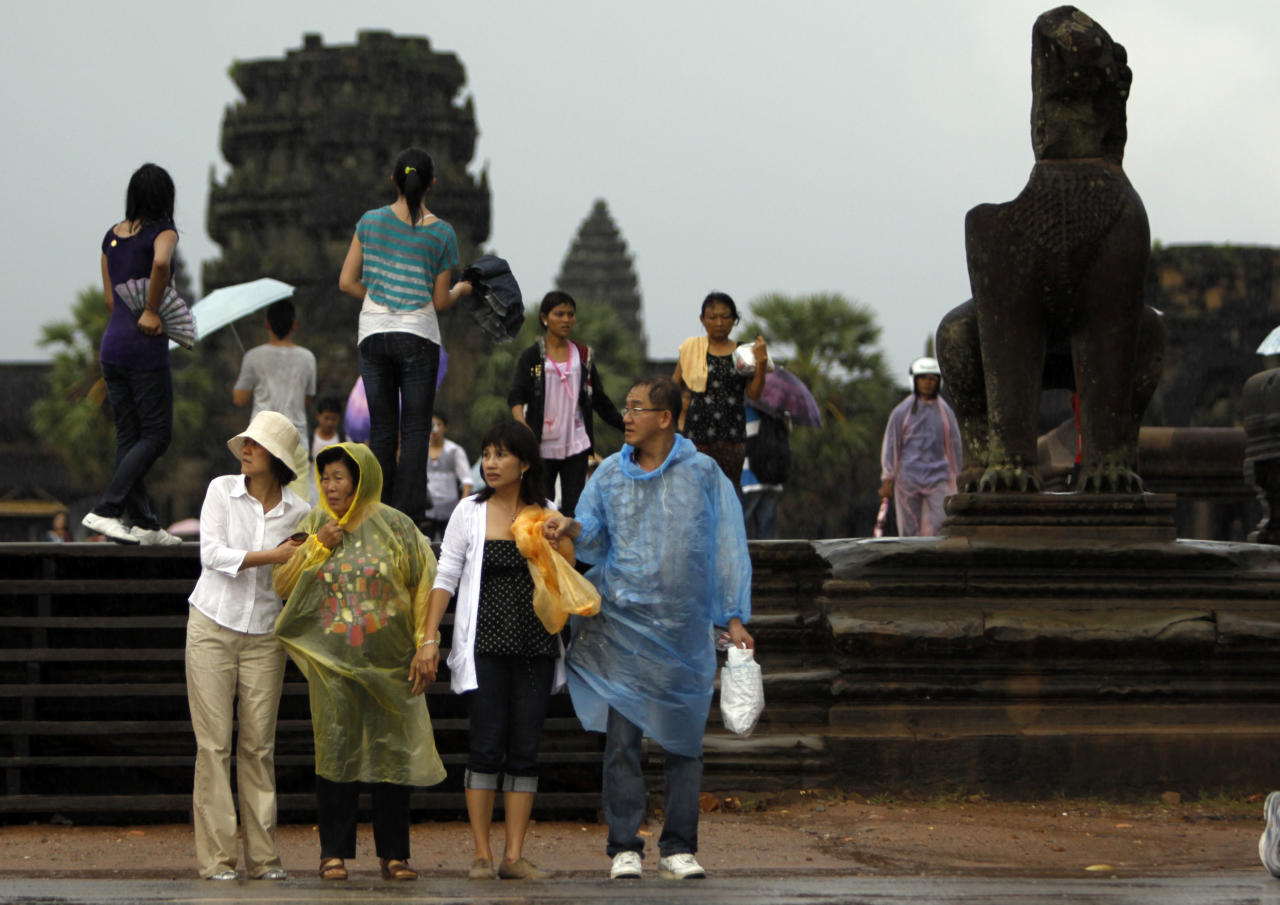Tourists walk through an entrance of the famed Angkor Wat in eastern Siem Reap province, some 230 kilometers (143 miles) northwest Phnom Penh, Cambodia, Saturday, July 2, 2011. Siem Reap is Cambodia's main tourist destination where famed Angkor temples are located. (AP Photo/Heng Sinith)