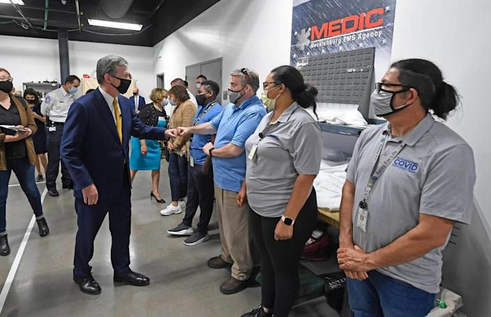 N.C. Gov. Roy Cooper greets workers who administer at-home COVID vaccines during a tour of the Mecklenburg County Vaccine Site at MEDIC Clinic on Wednesday, May 5, 2021.
