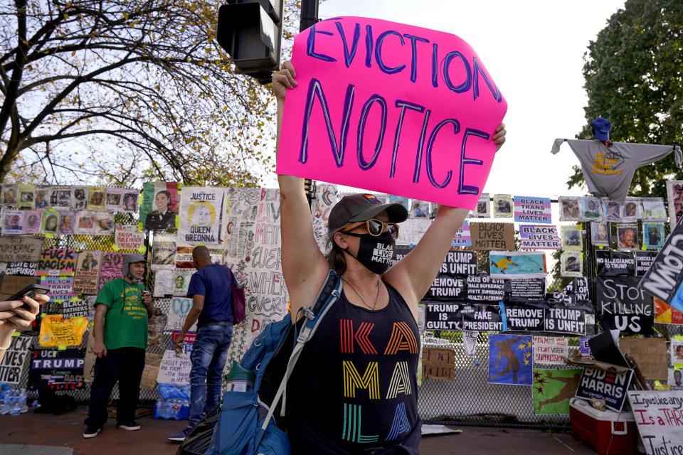 Jenn Katchmark, of Washington, holds up an eviction sign intended for Pres. Donald Trump while walking through Black Lives Matter Plaza, Thursday, Nov. 5, 2020, in Washington. (AP Photo/Jacquelyn Martin)