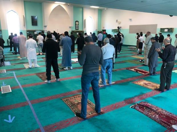 People gather for prayer at Windsor Islamic Association Mosque but stay six feet apart and with masks. (Jacob Barker/CBC - image credit)