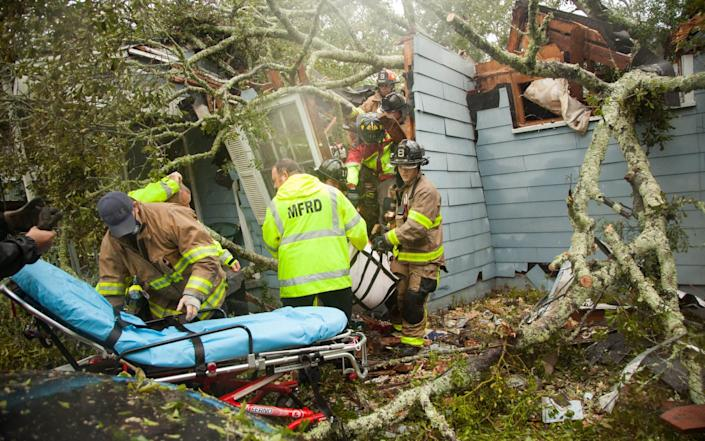 Rescue workers pick through the wreckage of a house in Mobile, Alabama, destroyed by a tree felled by Hurricane Sally - Leslie Spurlock/ZUMA Wire/Shutterstock /Shutterstock