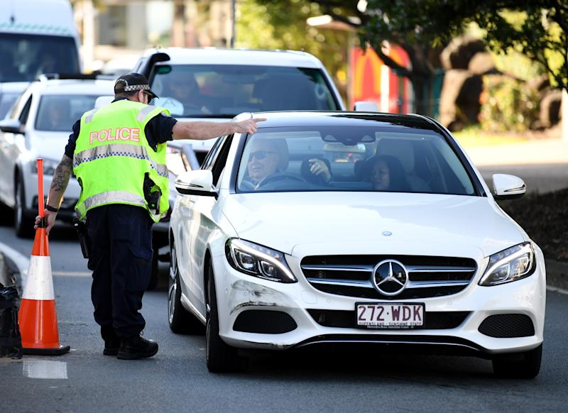 A police officer directs a car for further inspection at a check point on the Queensland-New South Wales border in Coolangatta on the Gold Coast.
