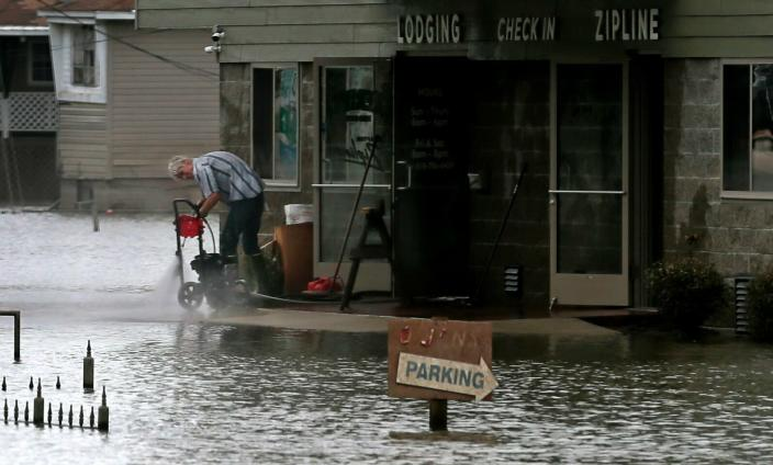 Handyman Jim Crow cleans an Aerie's Zipline building on Wednesday, June 19, 2019, in along Main Street in Grafton, Ill. On Wednesday, the level of the Mississippi River was 30.2 feet, having dropped about five feet from its crest at 35.17 on June 7. (Photo: Laurie Skrivan/St. Louis Post-Dispatch via AP)