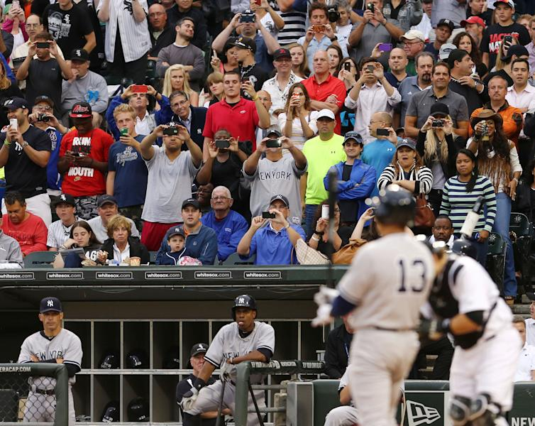 Fans watch and take pictures as New York Yankees' Alex Rodriguez bats for the first time in 2014 against the Chicago White Sox in a baseball game at US Cellular Field in Chicago on Monday, Aug.,5, 2013. (AP Photo/Charles Cherney)