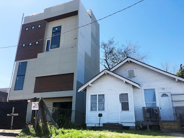 A newer apartment building built after Harvey (left) squeezes next to a pre-Harvey home in northeast Houston. (Photo: Sophie Kasakove)