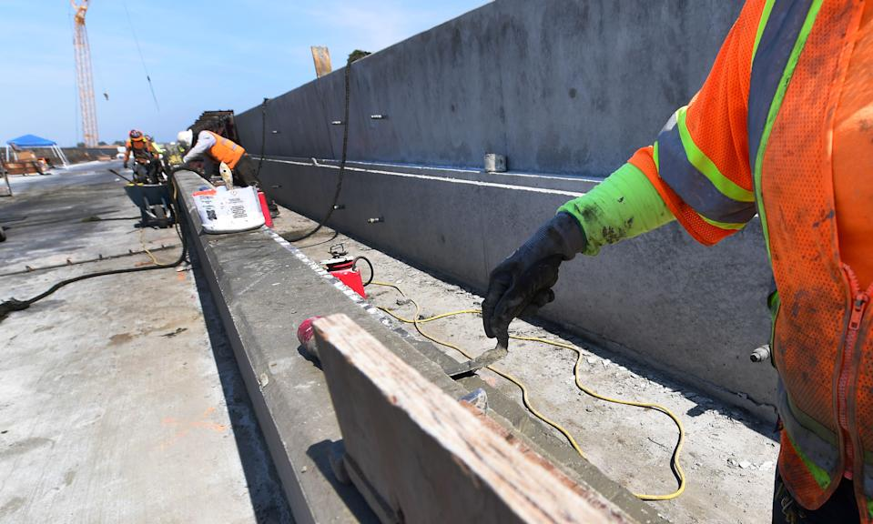 """Cement is laid by construction workers working on the San Joaquin River viaduct portion of the high-speed railway beside CA Highway 99 in Fresno, California, on May 8, 2019, amid ongoing construction of the railway in California's Central and San Joaquin Valleys. - In February, newly elected Governor Gavin Newsom announced that he was drastically revising downward the high-speed rail project to link Los Angeles to San Francisco in three hours, even though the plan was approved in a 2008 referendum. The federal government indicated that it was scrapping a $900 million subsidy due to """"chronic"""" construction delays. (Photo by Frederic J. BROWN / AFP)        (Photo credit should read FREDERIC J. BROWN/AFP/Getty Images)"""