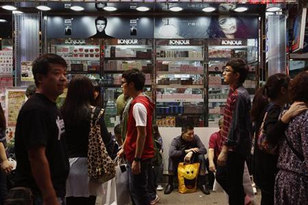 A mainland Chinese tourist rests outside a cosmetic store in Mong Kok district in Hong Kong