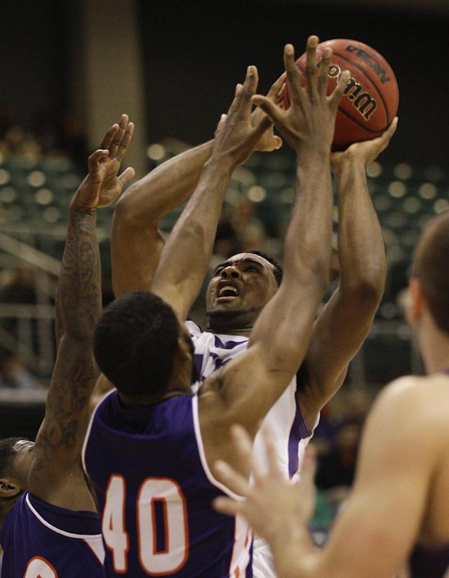 Stephen F. Austin's Desmond Haymon (25) takes a hard foul from Northwestern State's Marvin Frazier Jr. (40) as he drives to the basket during the second half of an NCAA college basketball game in the semifinal round of the Southland Conference tournament Friday, March 14, 2014, in Katy. (AP Photo/Bob Levey)