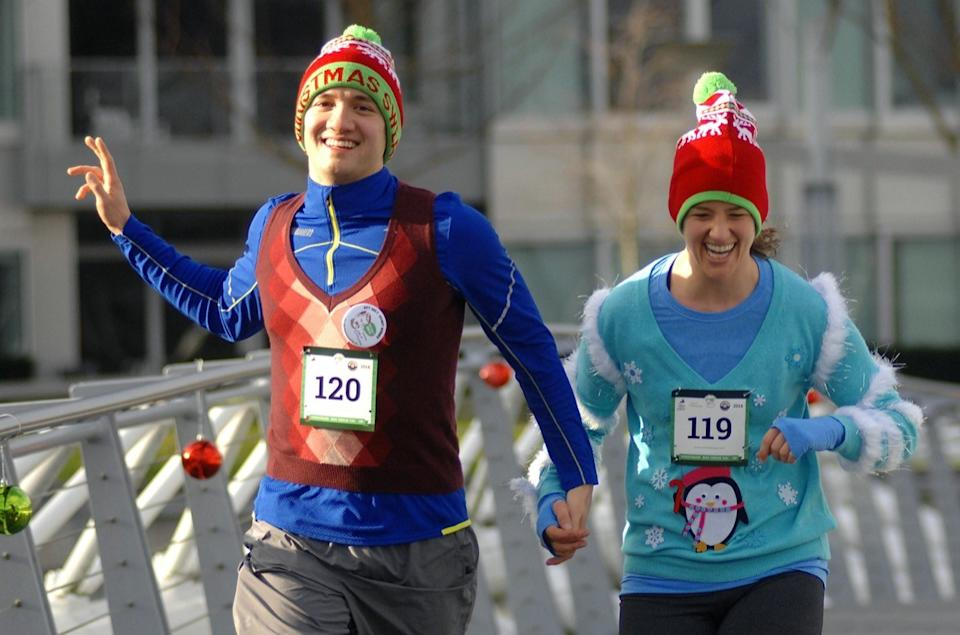 Young man and woman in Ugly Christmas Sweater race
