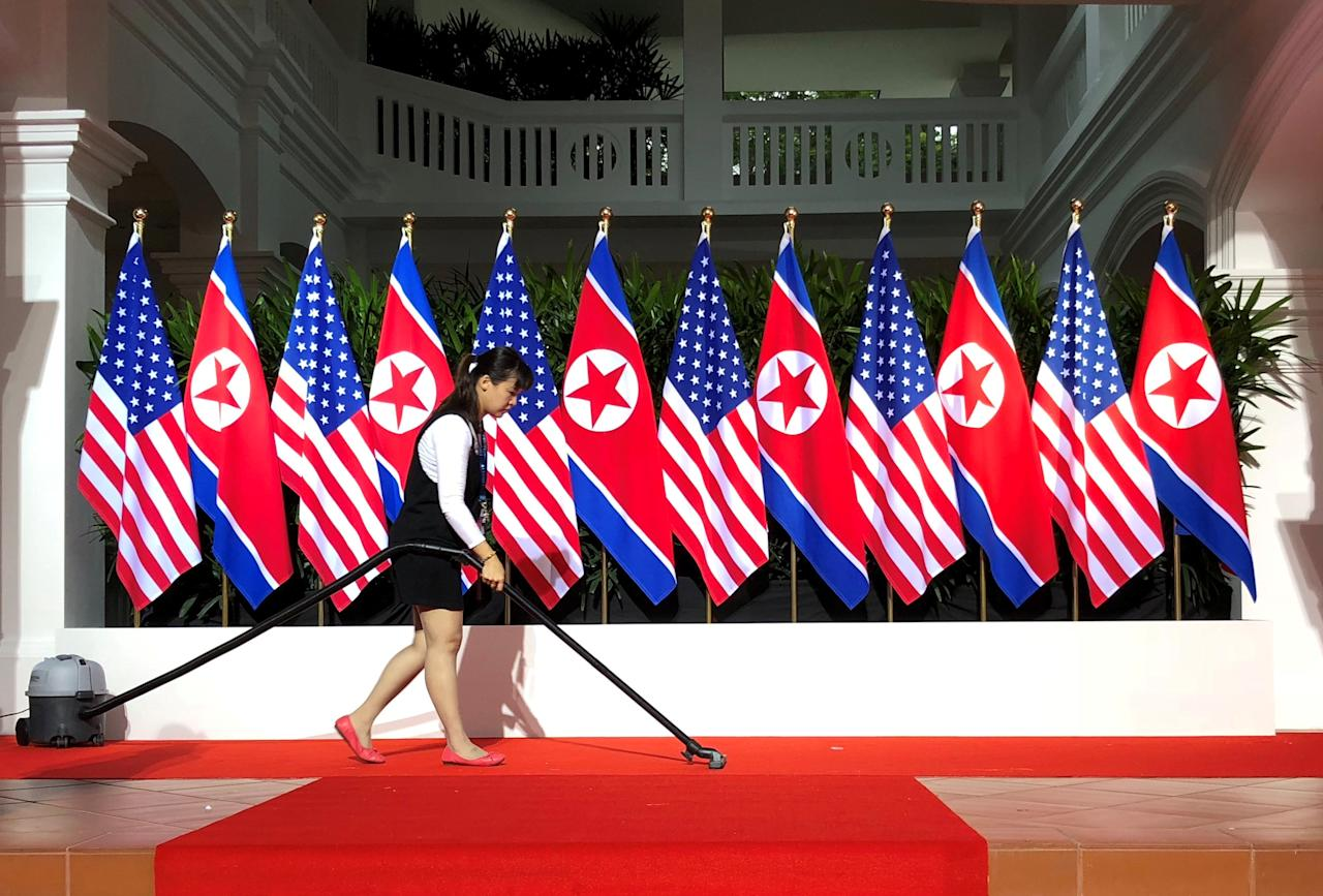 <p>A worker cleans the exact spot at Sentosa island's Capella Hotel where US President Donald Trump and North Korean leader Kim Jong Un were due to shake hands later on 12 June 2018. (PHOTO: Reuters) </p>