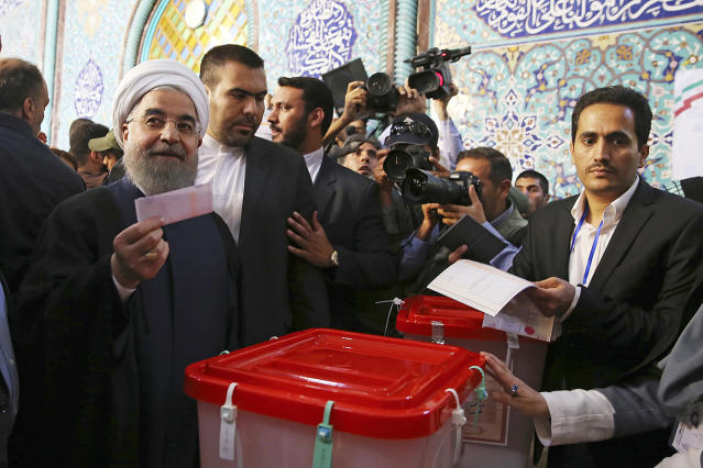 <p>In this photo released by official website of the office of the Iranian Presidency, President Hassan Rouhani holds his ballot while voting for the presidential and municipal councils election at a polling station in Tehran, Iran, May 19, 2017. Iranians began voting Friday in the country's first presidential election since its nuclear deal with world powers, as incumbent Hassan Rouhani faced a staunch challenge from a hard-line opponent over his outreach to the wider world. (Photo: Iranian Presidency Office via AP) </p>