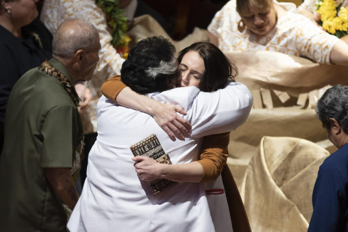New Zealand Prime Minister Jacinda Ardern, center right, is hugged during a ceremony in Auckland, Sunday, Aug. 1, 2021, to formally apologize for a racially charged part of the nation's history known as the Dawn Raids. The Dawn Raids are known as the time when the Pasifika people were targeted for deportation in the mid-1970s during aggressive home raids by authorities to find, convict and deport visa overstayers. (Brett Phibbs/New Zealand Herald via AP)
