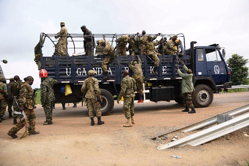 Uganda military personnel are seen on military and police trucks as they drive towards Juba, South Sudan, at Nimule border point on July 14, 2016 (AFP Photo/Isaac Kasamani)