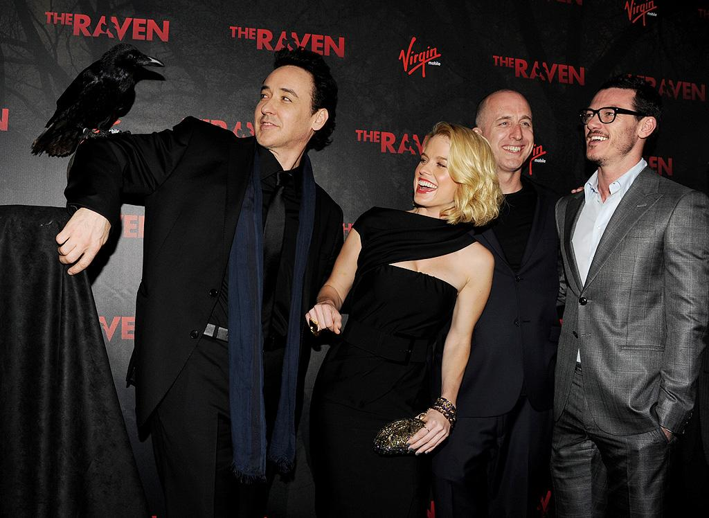 """<p class=""""MsoNormal"""">The publicists for the Edgar Allan Poe murder mystery """"The Raven"""" didn't miss an opportunity to promote the movie via the actual bird that shares the title. The animal posed with the film's lead John Cusack, who was joined by (L-R) co-star Alice Eve, director James McTeigue, and co-star Luke Evans at the premiere in downtown Los Angeles Monday night. (4/23/2012)</p>"""