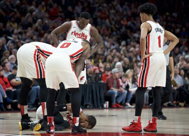 Portland Trail Blazers guard Rodney Hood is surrounded by teammates after tearing his Achilles tendon during the first half of the team's NBA basketball game against the Los Angeles Lakers in Portland, Ore., Friday, Dec. 6, 2019. (AP Photo/Craig Mitchelldyer)