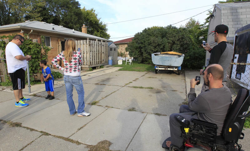 People photograph the driveway in Roseville, Mich., Wednesday, Sept. 26, 2012 where police plan to take soil samples from under   Friday after a tipster said it could be the final resting place of missing Teamsters leader Jimmy Hoffa. Roseville Police Chief James Berlin says a man claims to have seen a body buried there approximately 35 years ago. Berlin says the man believes it could be Hoffa. Hoffa disappeared in suburban Detroit in 1975, and his remains haven't been found. (AP Photo/Carlos Osorio)