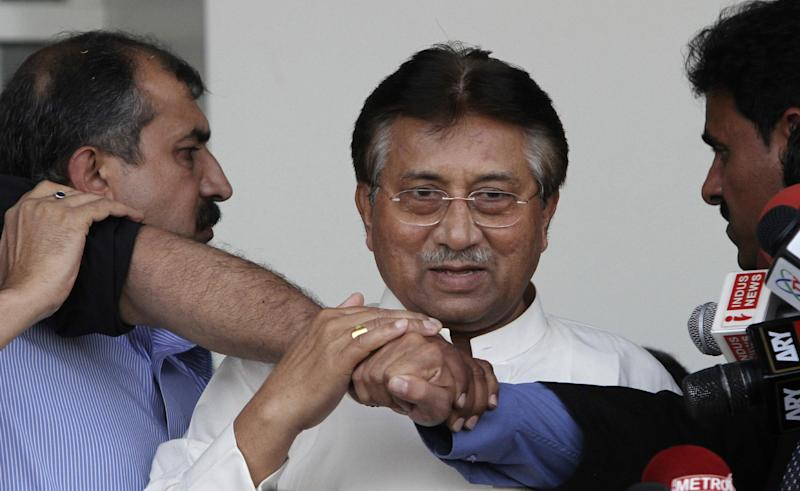 Former Pakistani President Pervez Musharraf, center, surrounded by guards, upon his arrival to Karachi airport, Pakistan, Sunday, March 24, 2013. Former Pakistani President Pervez Musharraf ended more than four years in self-exile Sunday with a flight to his homeland, seeking a possible political comeback in defiance of judicial probes and death threats from Taliban militants. (AP Photo/Shakil Adil)
