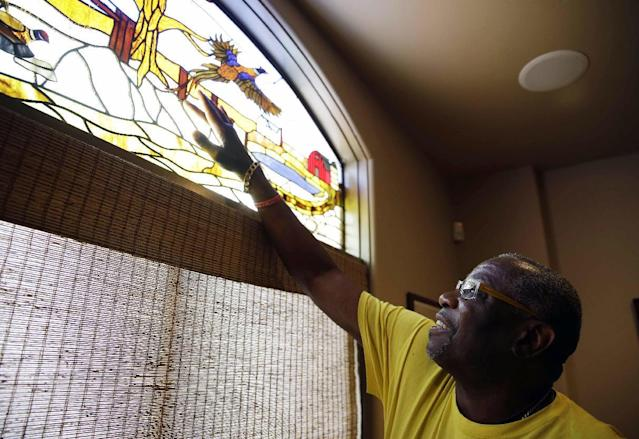In this March 13, 2014 photo, light filters through a stained glass window depicting a hunting scene onto Dusty Baker at his home in Granite Bay, Calif. Out of uniform for the first time since taking 2007 off between managerial jobs with the Cubs and Reds, Baker is not slowing down much from his pressure-packed days in the dugout. While his sport is still close to his heart despite the sting of his firing after last season in Cincinnati, Baker is working on more than a half-dozen projects at once out of his Sacramento-area home. (AP Photo/Eric Risberg)