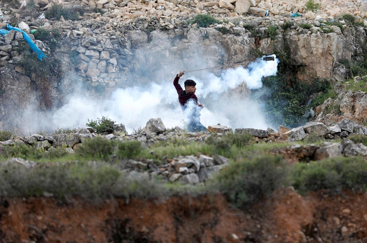 A Palestinian demonstrator returns a tear gas canister fired by Israeli troops during clashes at a protest against Trump's decision on Jerusalem, near Ramallah, in the occupied West Bank March 16, 2018. REUTERS/Mohamad Torokman