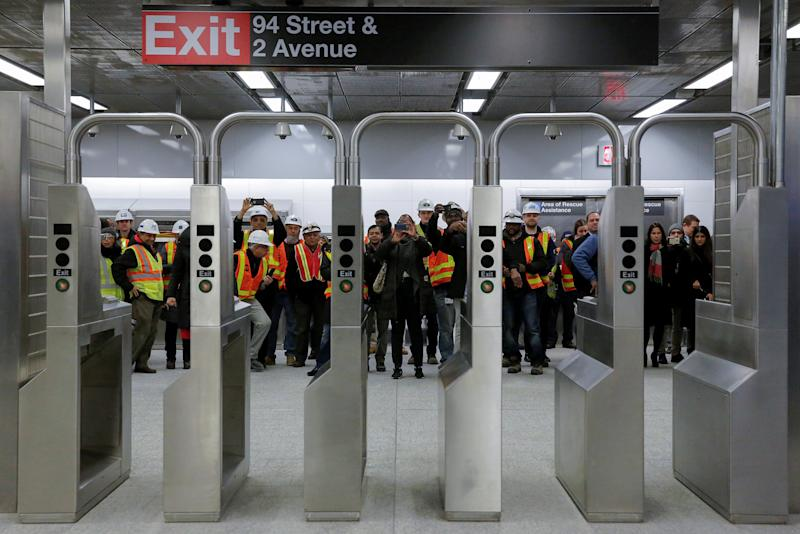 Workers take photos through the turnstyles at the 96th Street Station during a preview event for the Second Avenue subway line in Manhattan, New York City, U.S.