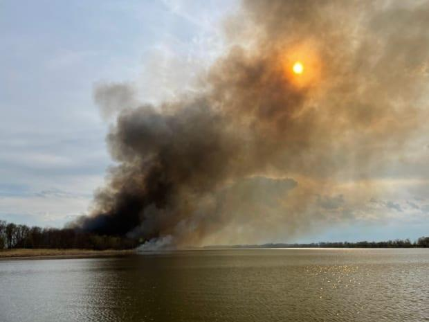 Black smoke floats into the sky as a wildfire burns on the east bank of the Red River, across from Breezy Point, Man.