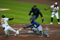 Baltimore Orioles' Anthony Santander (25) slides into home as Seattle Mariners catcher Luis Torrens tries to apply the tag during the third inning of the second game of a baseball doubleheader, Tuesday, April 13, 2021, in Baltimore. The ball kicked away from from Torrens and Santander was ruled safe. On the play, Santander, Freddy Galvis and DJ Stewart scored on a bases loaded double by Maikel Franco. (AP Photo/Julio Cortez)