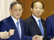 Japanese Prime Minister Yoshihide Suga, left, also the Liberal Democratic Party party leader, poses with the ruling party's senior officials, including Toshihiro Nikai, right, at the party headquarters in Tokyo, on Sept. 15, 2020. Prime Minister Suga came to office on a surge of popularity, pledging to combat the coronavirus and fix the languishing economy. Now his support ratings have plunged amid flaring virus outbreaks and scandals within the ruling party, even as the economy appears to be recovering. (Kyodo News via AP)