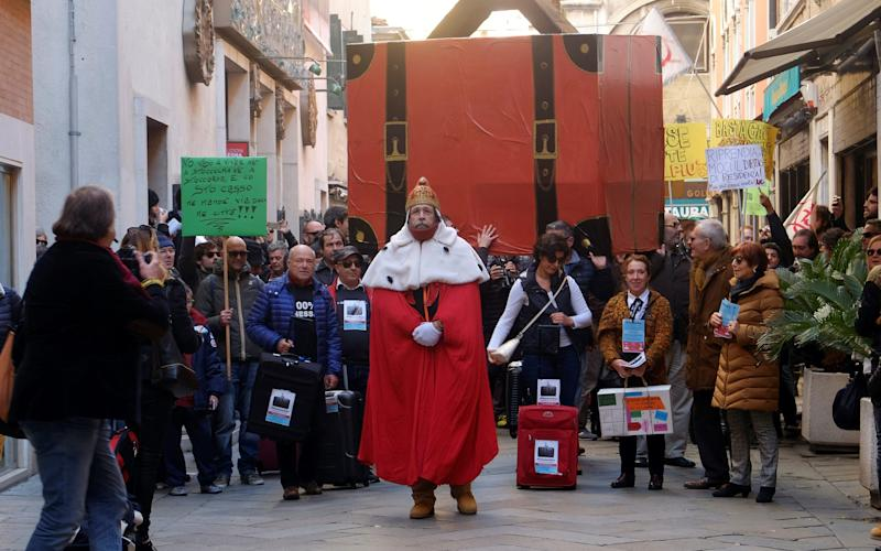 Venetians carry a huge suitcase in a symbolic protest about the number of residents packing their bags and leaving the lagoon city for good. - Credit: Manuel Silvestri/Reuters