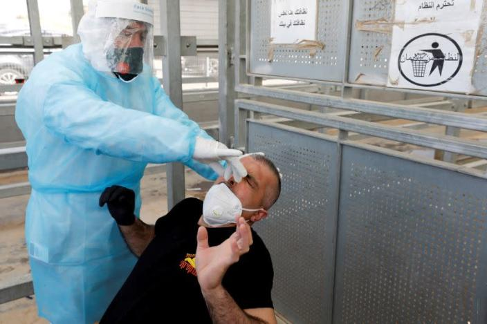 FILE PHOTO: Palestinian worker return from Israel amid concerns about the spread of the coronavirus disease, in the Israeli-occupied West Bank