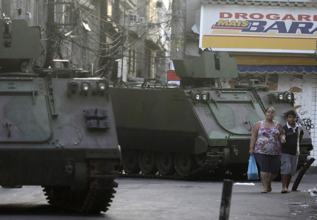 Residents walk past Brazilian Navy armored vehicles during an operation at the Mare slums complex in Rio de Janeiro