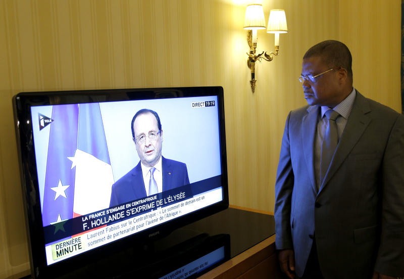 """Prime Minister of the Central African Republic Nicolas Tiangaye watches French President Francois Hollande on TV, as he announces he would double the number of troops in the former French colony, possibly within hours, in Paris, Thursday, Dec. 5, 2013. In his first reaction to the French move, Tiangaye told The Associated Press that he sees it """"very positively"""" and that he had wanted a """"firm reaction from France."""" The U.N. Security Council authorized an intervention force to prevent a bloodbath between Christians and Muslims, as fighting swept through the capital of Central African Republic on Thursday, leaving nearly one hundred people dead and posing the biggest threat yet to the country's new government. (AP Photo/Christophe Ena)"""