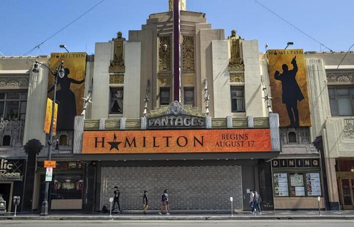 HOLLYWOOD, CA - JULY 01, 2021: Pedestrians walk past the Pantages Theatre, on Hollywood Blvd. in Hollywood, where the play, Hamilton, is scheduled to resume on August 17, 2021. Hollywood, the neighborhood, is attempting to recover from pandemic-related business closures and damage caused last year by rioters among demonstrators protesting the murder of George Floyd. (Mel Melcon / Los Angeles Times)