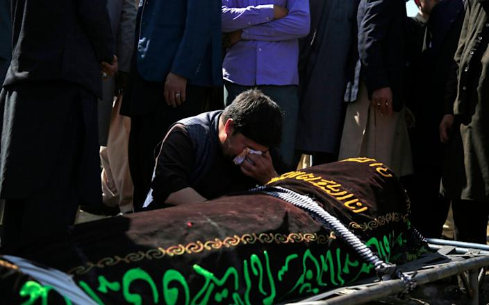 A man cries over the body of one of the victims of the deadly bombings - Mariam Zuhaib/AP