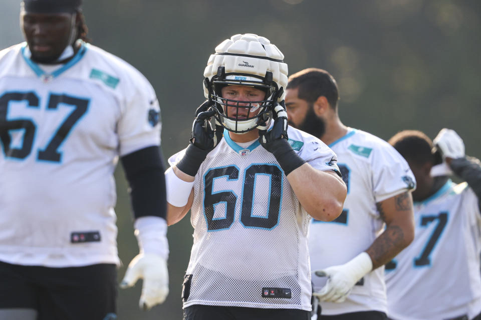 Carolina Panthers center Pat Elflein (60) adjusts his helmet, which is covered by a Guardian Cap during practice at the NFL football team's training camp in Spartanburg, S.C., Tuesday, Aug. 10, 2021. (AP Photo/Nell Redmond)