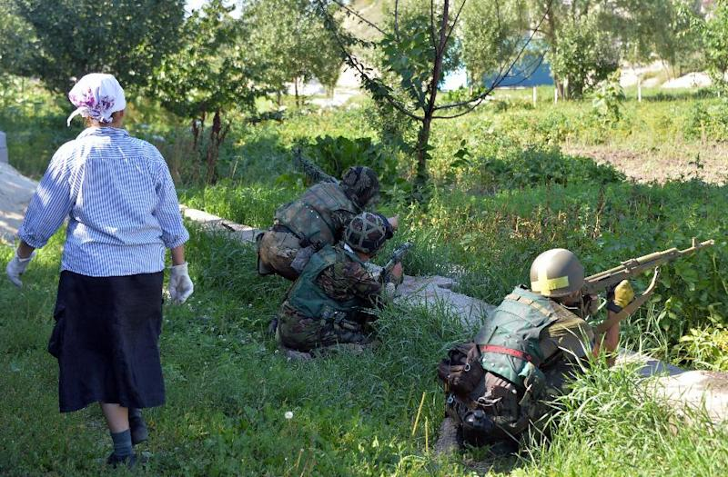 An elderly resident of the eastern Ukrainian city of Lysychansk walks past Ukrainian service men patroling the outskirts of the city on July 26, 2014