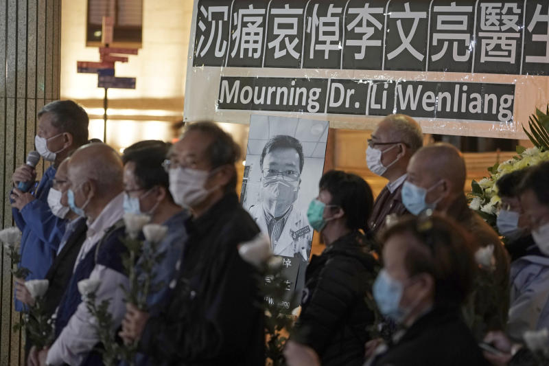 People wearing masks, attend a vigil for late Chinese doctor Li Wenliang, in Hong Kong, Friday, Feb. 7, 2020. The death of a young doctor who was reprimanded for warning about China's new virus triggered an outpouring Friday of praise for him and fury that communist authorities put politics above public safety. (AP Photo/Kin Cheung)