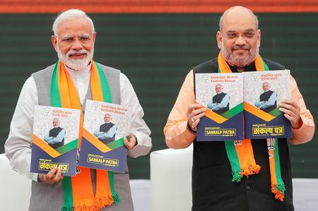 Indian Prime Minister Narendra Modi and chief of India's ruling Bharatiya Janata Party (BJP) Amit Shah, display copies of their party's election manifesto for the April/May general election in New Delhi, India, April 8, 2019. REUTERS/Adnan Abidi