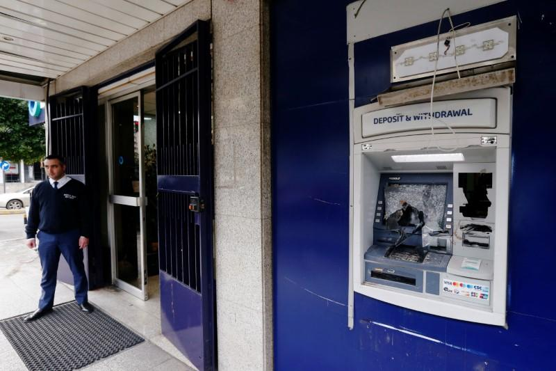 A security guard stands near a damaged ATM machine outside BBAC bank in Beirut