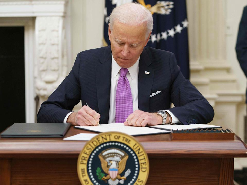 <p>Joe Biden signs executive orders as part of the Covid-19 response in the State Dining Room of the White House in Washington</p> (AFP via Getty Images)