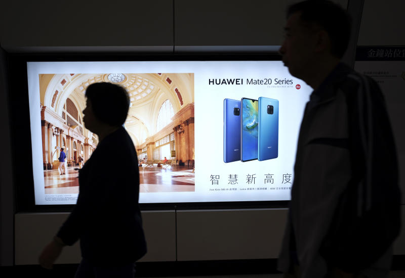 People walk past an advertisement for Huawei at a subway station in Hong Kong Thursday, Dec. 5, 2018. Canadian authorities said Wednesday that they have arrested Huawei's chief financial officer Meng Wanzhou for possible extradition to the United States. (AP Photo/Vincent Yu)