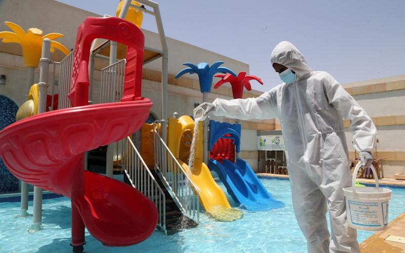 A worker wearing a protective suit sterilizes the chalet pool rented by Saudi families in Riyadh, Saudi Arabia - Reuters