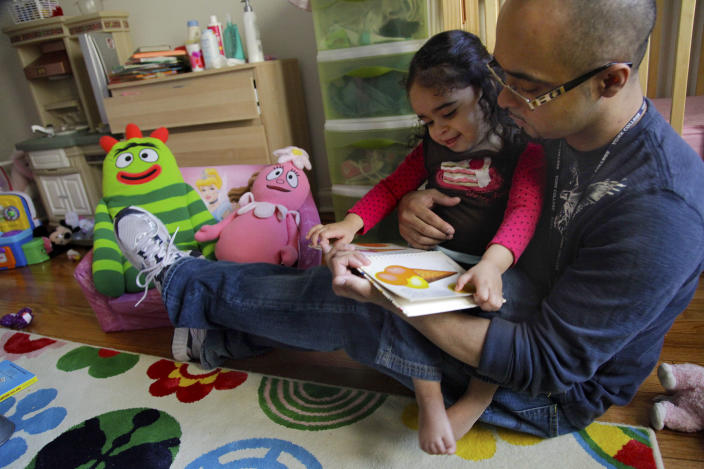 Christopher Astacio reads with his daughter Cristina, 2, recently diagnosed with a mild form of autism, in her bedroom on Wednesday, March 28, 2012 in New York. Autism cases are on the rise again, largely due to wider screening and better diagnosis, federal health officials said Thursday, March 2012. (AP Photo/Bebeto Matthews)