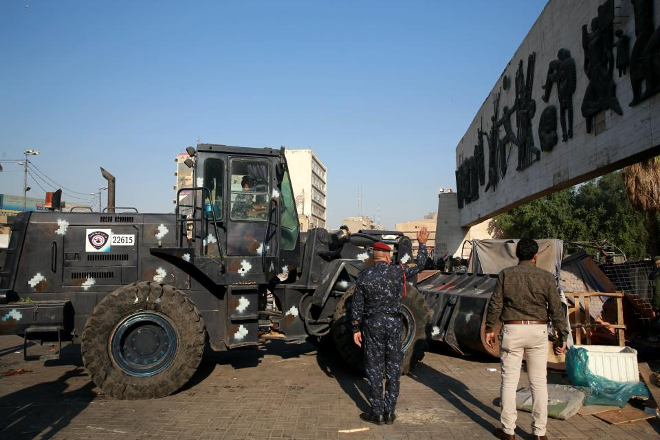 Security forces remove anti-government protesters' tents at protesters' site in Tahrir Square, Baghdad, Iraq, Saturday, Oct. 31, 2020. (AP Photo/Khalid Mohammed)